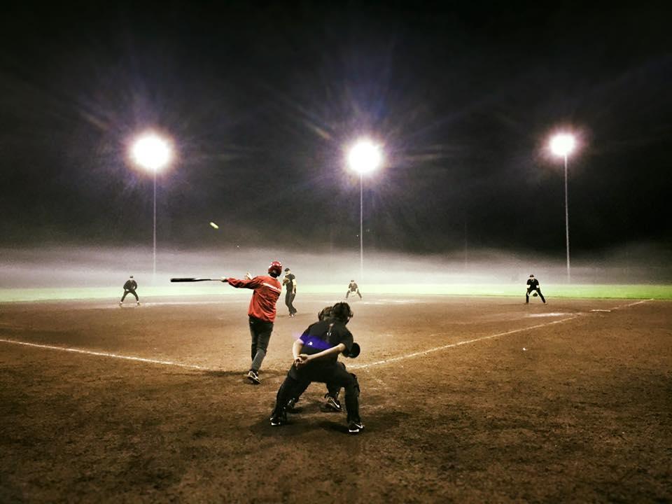Slagman herensoftbal slaat bal weg tijdens een avondwedstrijd